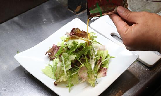 葉野菜の水気を切り豆腐の上にのせ、まぜるめんつゆをかける