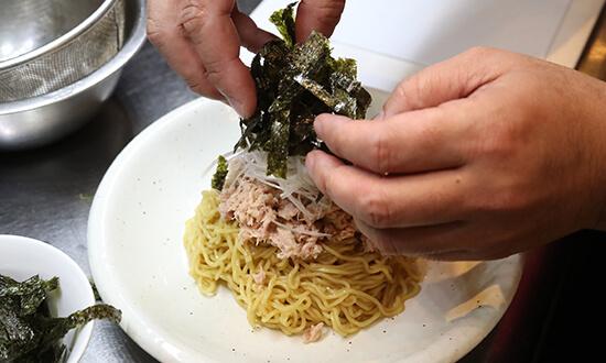 皿に麺を盛り、ツナ、白髪葱、炒りごま、揉み海苔をのせて完成