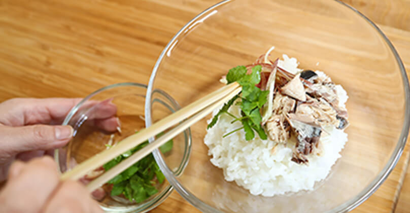 ご飯を器によそい、ご飯の上にほぐしておいたさばの水煮、みょうが、三つ葉をのせる。